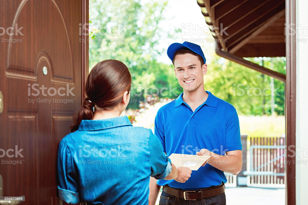 Postman delivering a mail Postman standing at the door of the house and holding a letter for young woman. 2015 Stock Photo