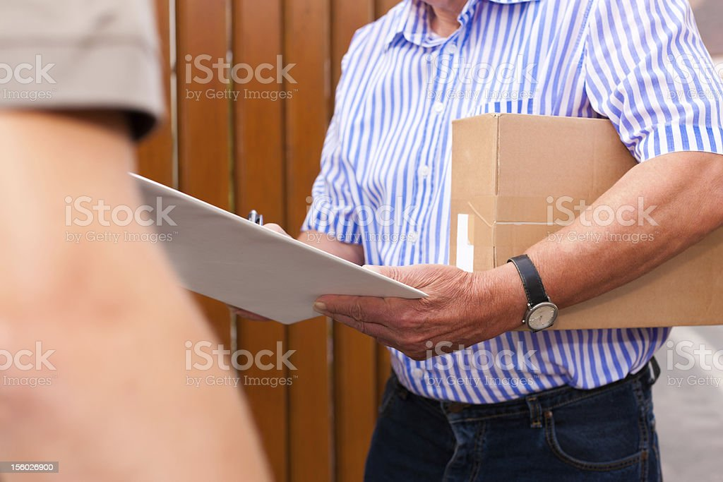 Postman delivering a package to customer in front of house royalty-free stock photo