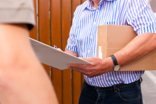 Postman Delivering A Package To Customer In Front Of House Stock Photo - Download Image Now