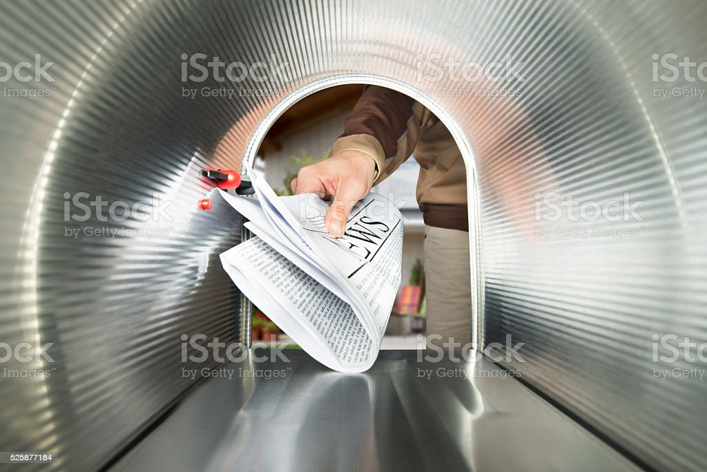 Postman Delivering Newspaper View From Inside The Mailbox stock photo