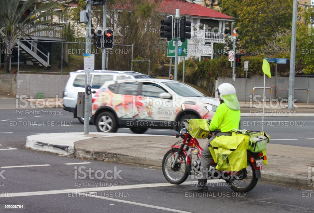 A postman from Australia Post delivers mail on a motorbike in Brisbane Australia with Queensland houses in background stock photo
