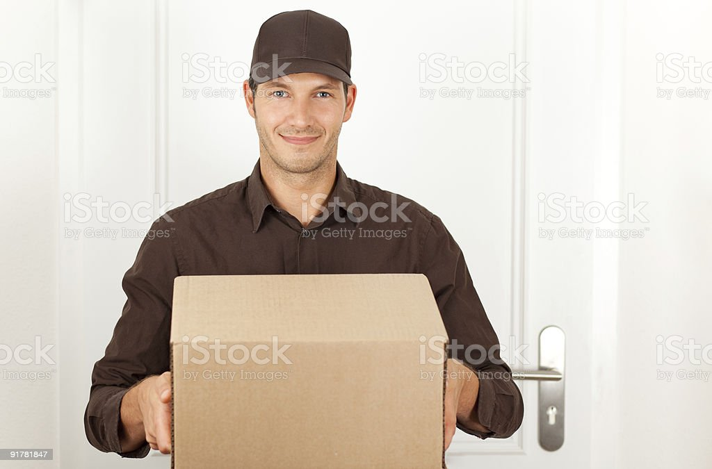 postman in formal brown clothes with packet box stock photo