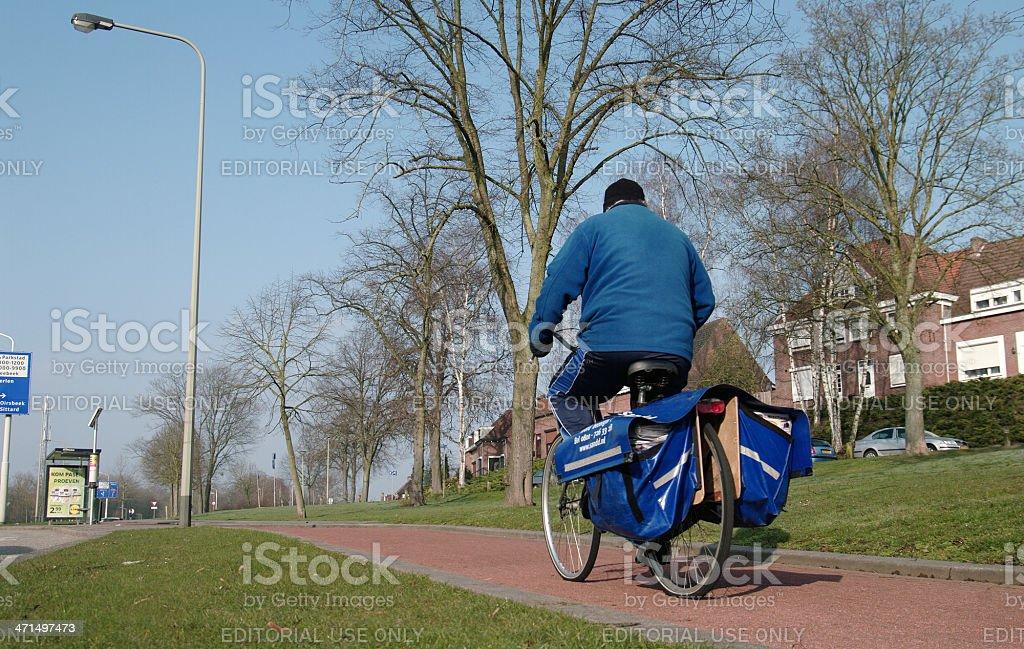Postman on his bike royalty-free stock photo