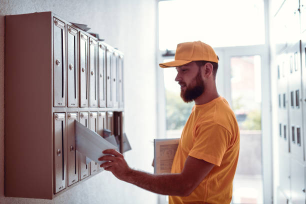 Postman Putting Letter In Mailbox stock photo