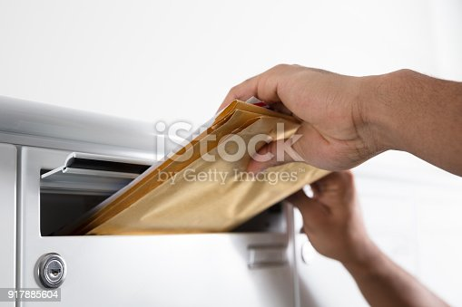 istock Postman Putting Letters In Mailbox 917885604