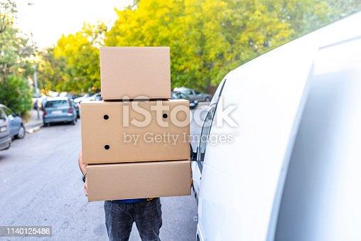 635967404 istock photo Postman with parcel box. 1140125486