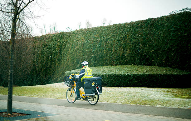 postman worker on bicycle on cold day - postal worker 뉴스 사진 이미지