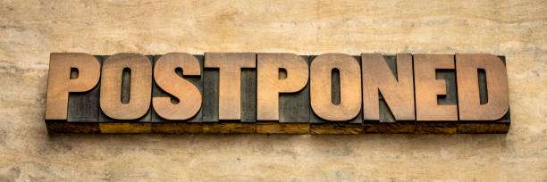 postponed word abstract in wood type stock photo