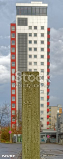 istock Posts of concrete in the foreground with a large ugly concrete tower in the background 909508684