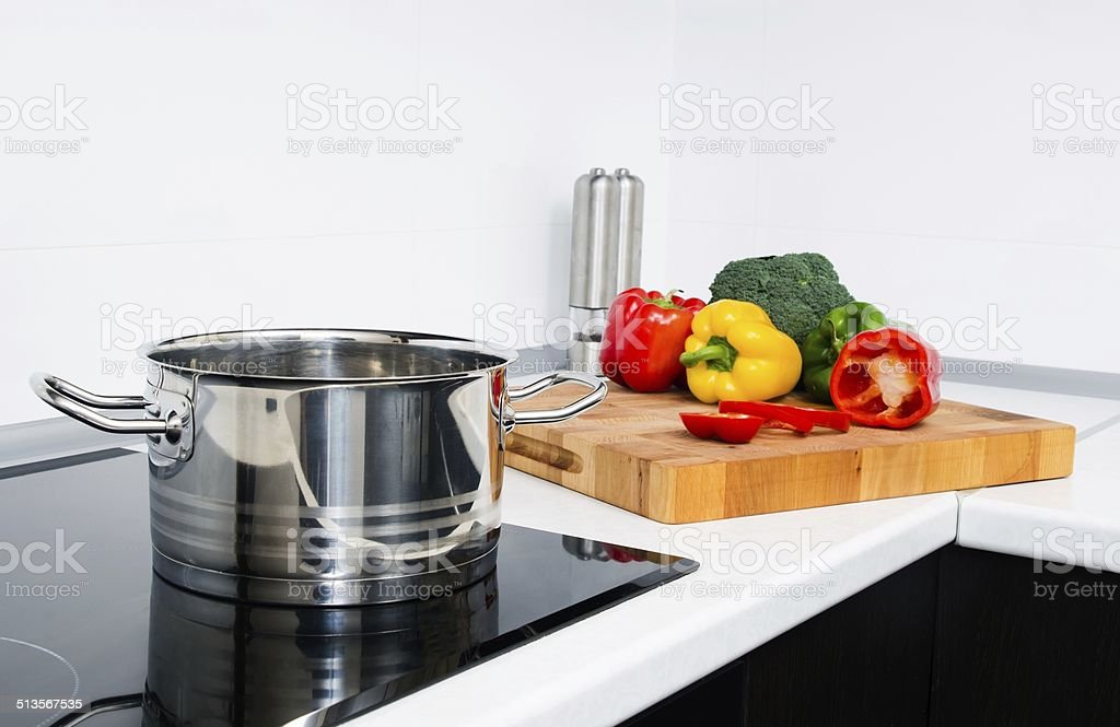 Pot and vegetables in modern kitchen with induction stove stock photo