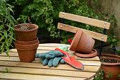 Pot de fleurs et gant en latex posés sur une table de jardin