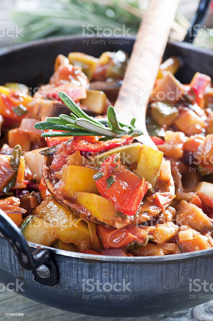 A pot full of ratatouille with a wooden spoon royalty-free stock photo
