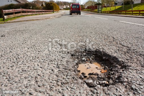 istock Pot hole in residential road surface 178575057
