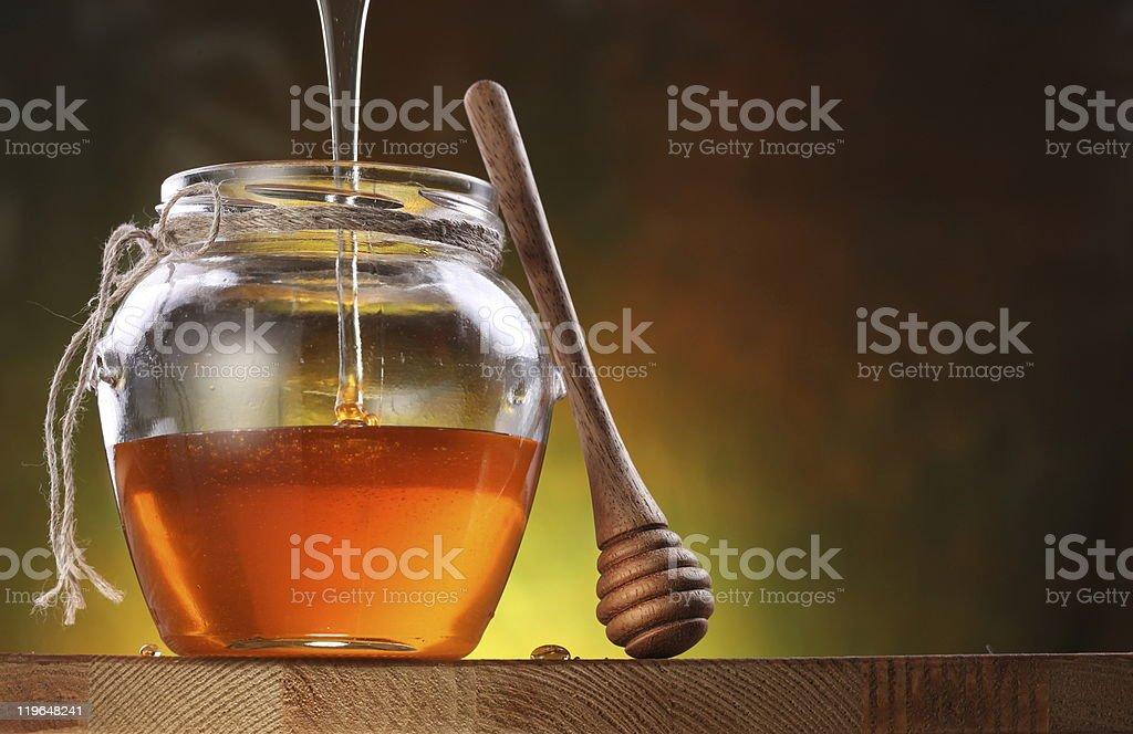 Pot is being filled with honey and a drizzler. stock photo