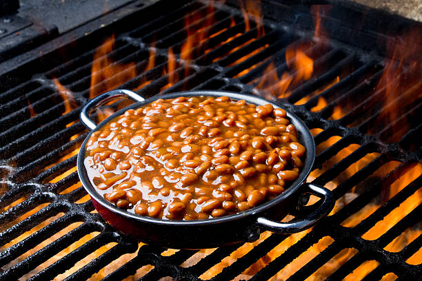 Pot of Baked Beans on a Flaming Grill stock photo
