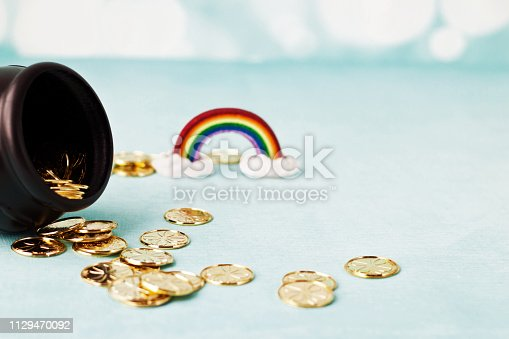 artificial coins spilling out of black pot that makes a pathway to a rainbows end, soft focus and dream like scene