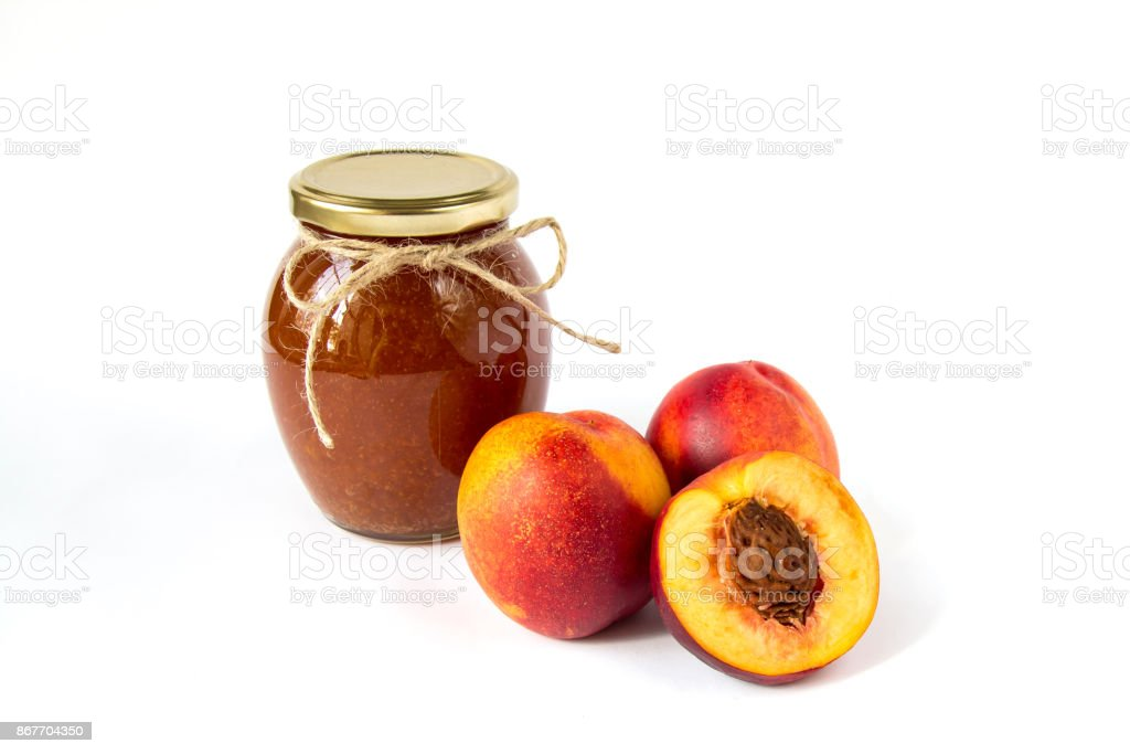 Pot of jam on white background with ripe appetizing half cut peaches stock photo