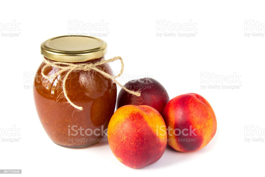 Pot of jam on white background with ripe appetizing peaches stock photo