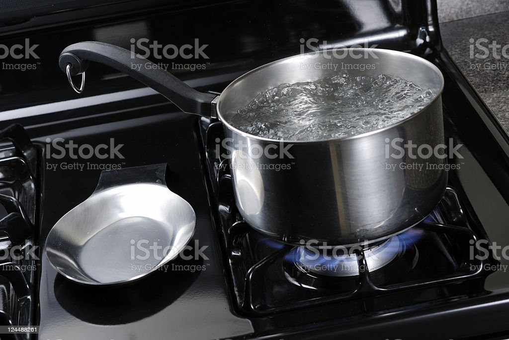 Pot of water boiling on a black natural gas stove. stock photo
