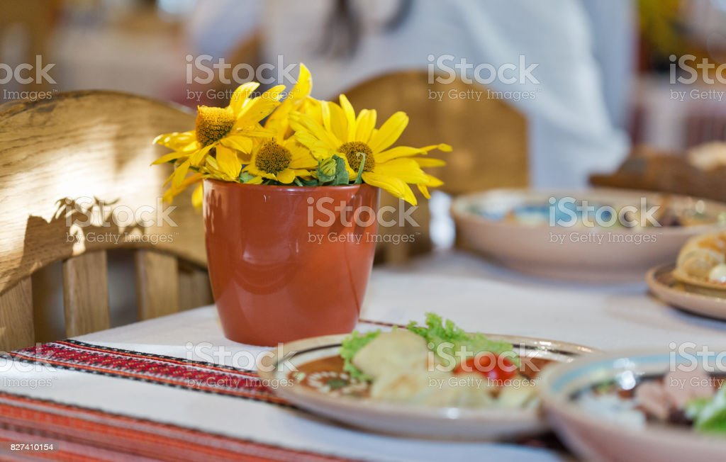 A pot of yellow daisies on a dinner table stock photo