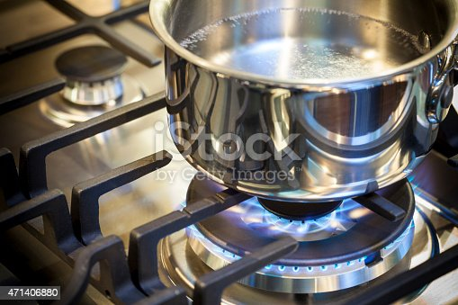 Gas burner on stove with flame on stainless steel surface showing heat ready for cooking food. Stainless steal pot on burner cooking food.