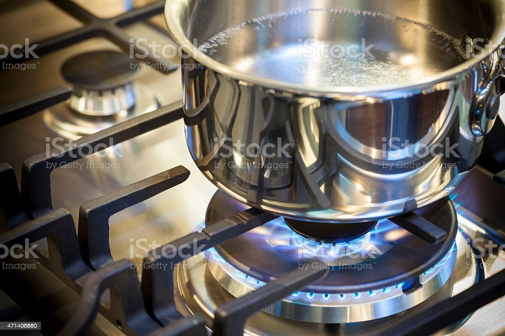 Pot on stove with gas burner and flame stock photo