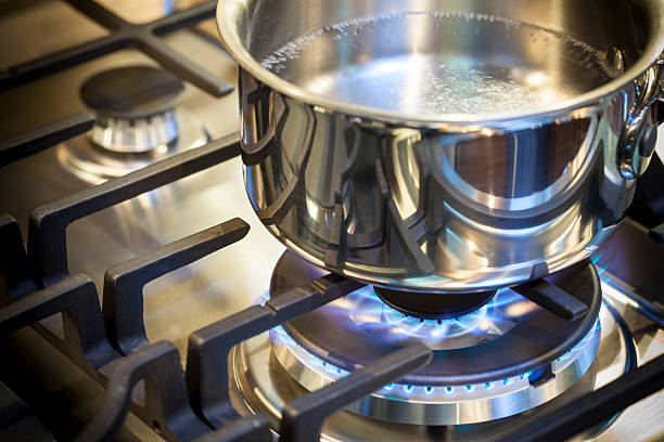 Pot on stove with gas burner and flame Gas burner on stove with flame on stainless steel surface showing heat ready for cooking food. Stainless steal pot on burner cooking food. stove stock pictures, royalty-free photos & images