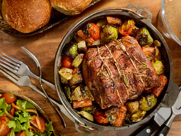 Pot Roast Dinner Roast smothered in roasted Garlic, olive oil, fresh Herbs, sea salt and pepper with asparagus, baby potatoes, carrots and roasted to perfection-Photographed on Hasselblad H3D2-39mb Camera roast beef stock pictures, royalty-free photos & images
