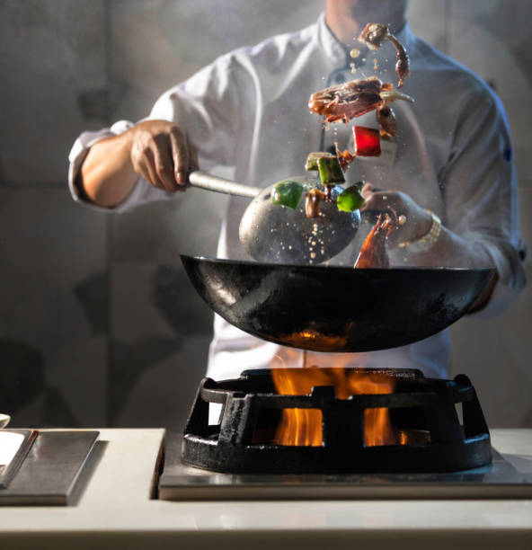 Pot with fire, chief cooking. stock photo