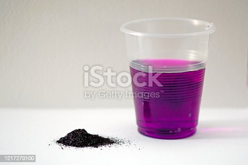 Potassium permanganate powder on a white background. Black powder potassium permanganate and a plastic glass with rose water. A solution of potassium permanganate in water.