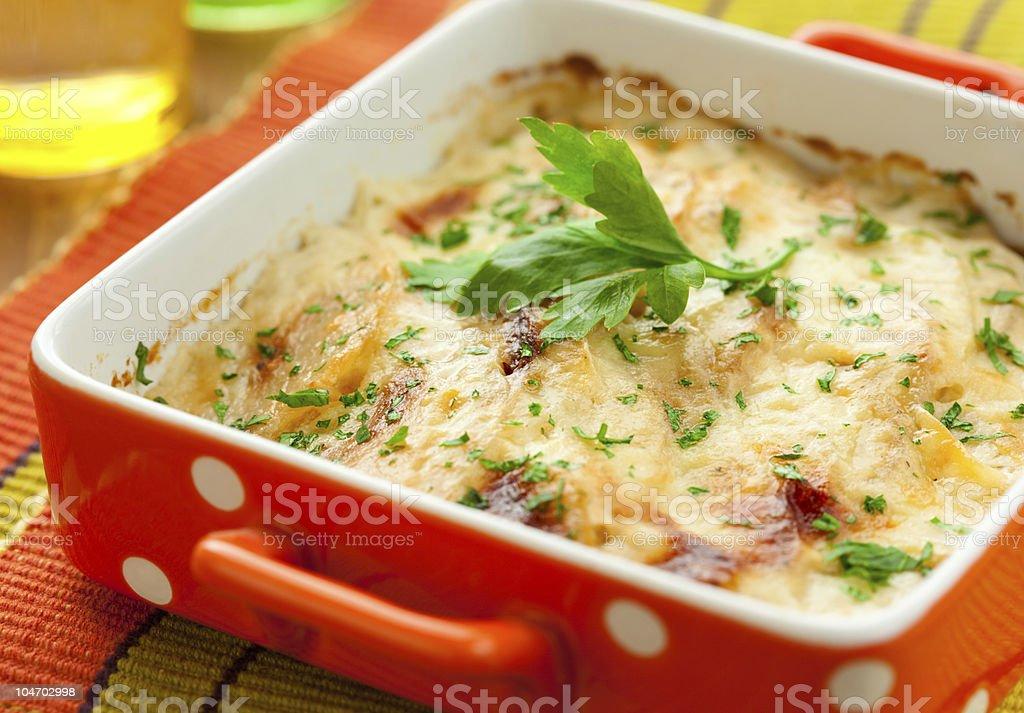 A potato and kohlrabi gratin dish in a red polka dot dish royalty-free stock photo