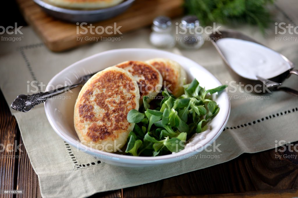 Potato cakes with cheese, yogurt sauce and lettuce leaf. stock photo