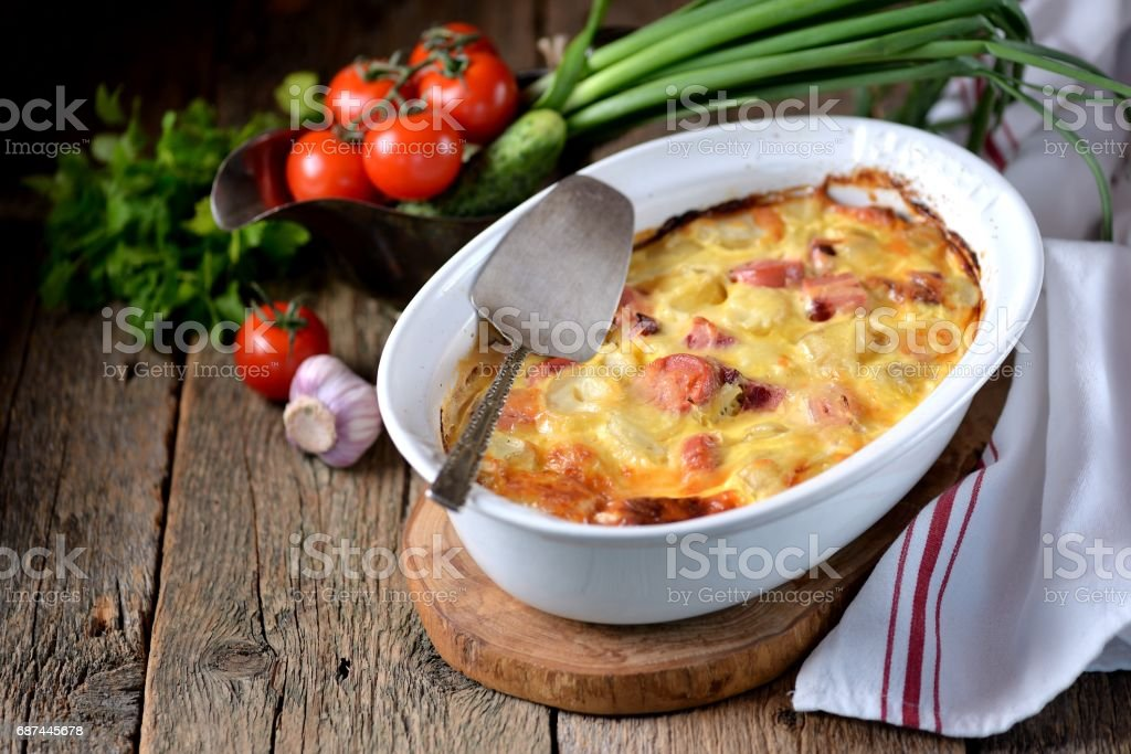 Potato casserole with sausages, onions and cheese on an old wooden background. Rustic style. stock photo