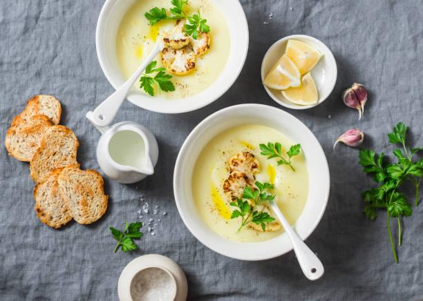 kartoffel-blumenkohl-suppe pürieren auf einem grauen hintergrund, ansicht von oben. vegetarische ernährung-konzept - knoblauchkartoffeln stock-fotos und bilder