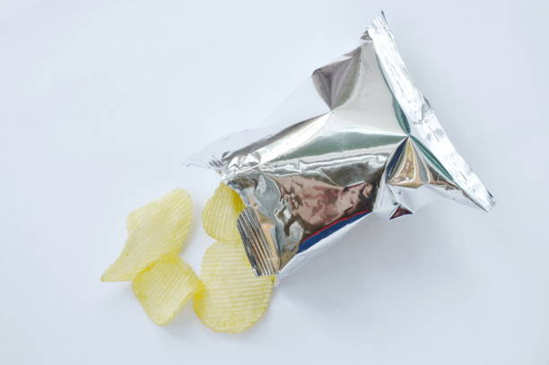 potato chip pouring from packaging on white background - crisp packet stock photos and pictures