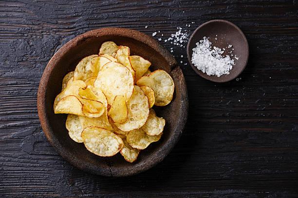 Potato chips and salt stock photo
