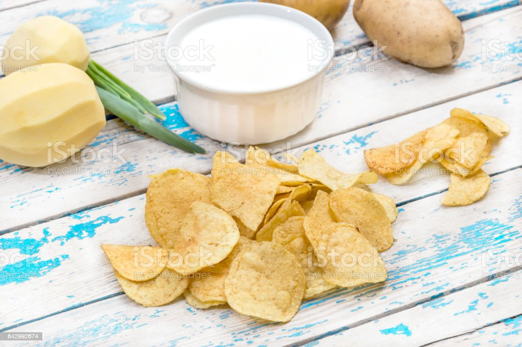 Potato chips, bowl with sour cream and raw potato on the table. stock photo
