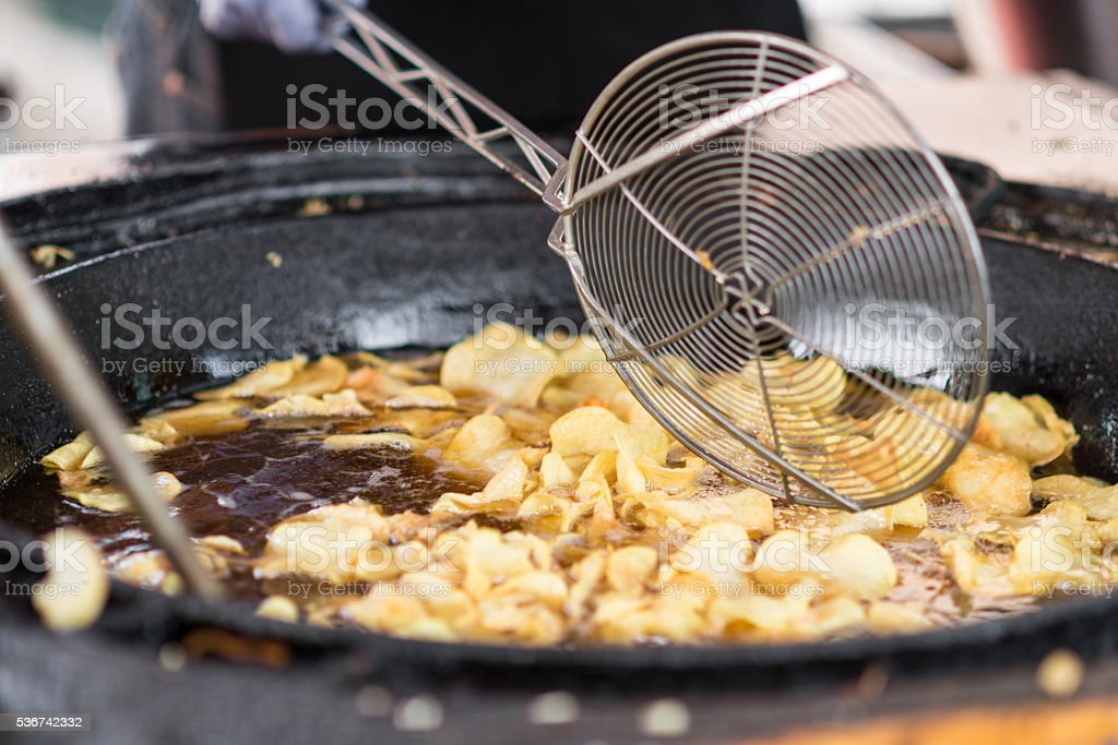 potato chips deep-fry swimming in oil on a market stock photo