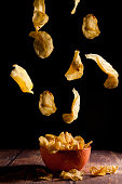 potato chips falling into an orange ceramic bowl on a wooden table and black background