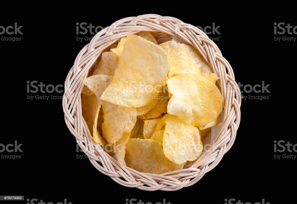 Potato chips in a basket made of rattan on a black background. stock photo