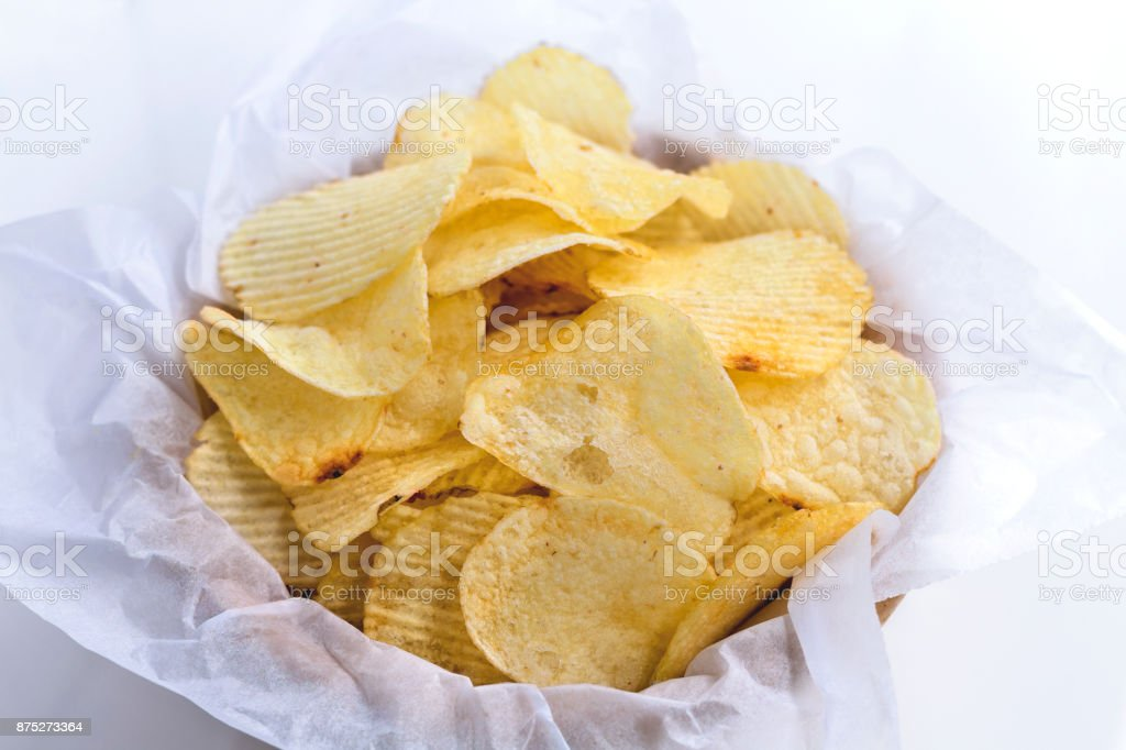 Potato chips in a bowl made of wood on a black background. stock photo