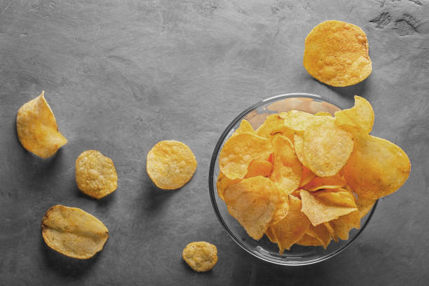 Potato chips in bowl with tomato juice in glass – Foto