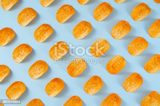 istock Potato Chips on Blue Background 860044654