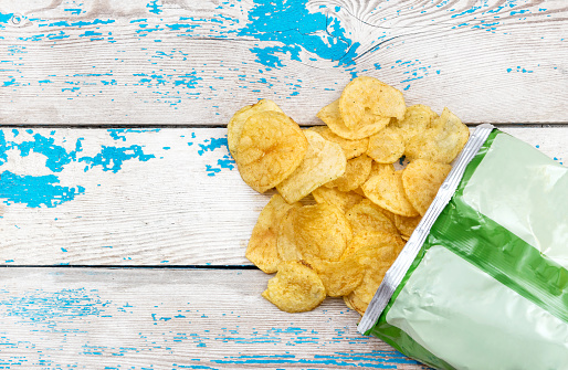 istock Potato chips scattered with packaging on the table. Top view. 692931230
