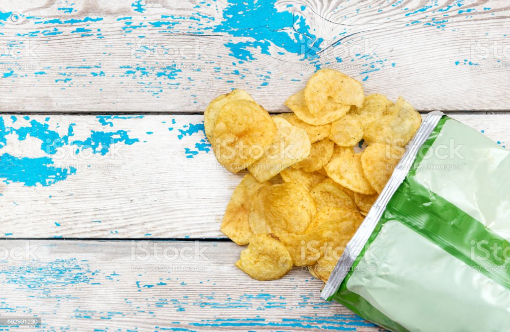 Potato chips scattered with packaging on the table. Top view. stock photo