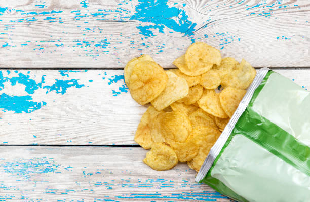 potato chips scattered with packaging on the table. top view. - crisp packet stock photos and pictures