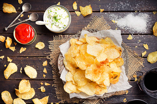 Potato chips with dipping sauces on a rustic table stock photo