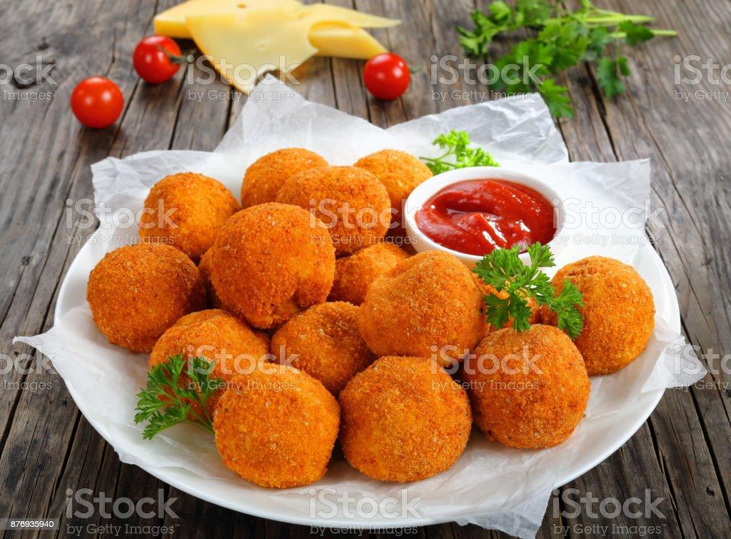 aardappelkroketten met ketchup op plaat foto