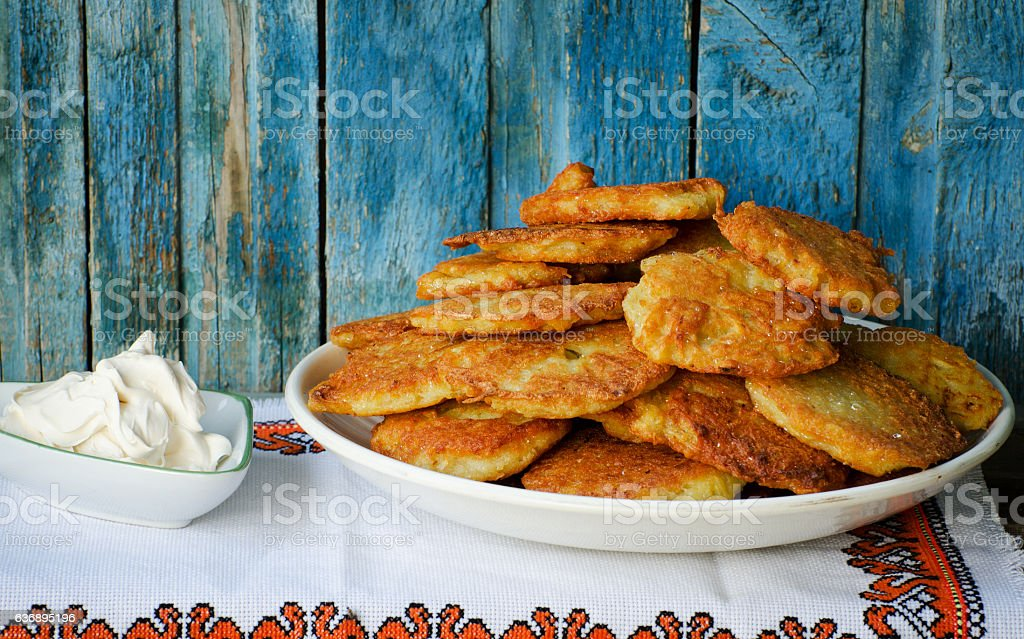Potato fritters in a large dish, sour cream stock photo