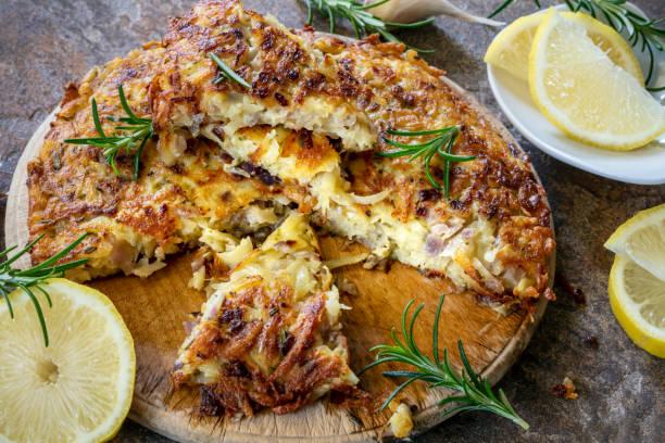Potato, garlic and rosemary frittata, sliced, with lemon. stock photo